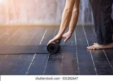 Yoga concept. Young yogi men rolling mat after a yoga on black wooden floor