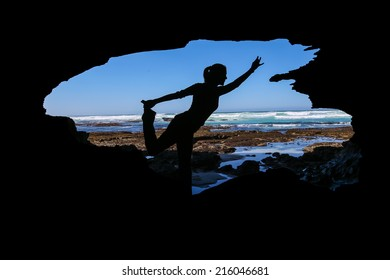 Yoga Dancer's Pose The silhouette of a woman doing yoga in a cave by die ocean. She's in the dancer's pose. Blue sky and waves breaking