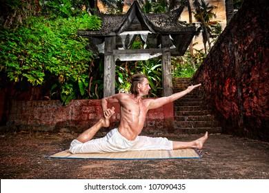 Yoga eka pada raja kapotasana by fit man in white trousers near stone temple in tropical forest