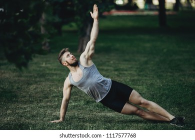 Yoga, endurance training, street workout, fitness, sport, outdoor activity, healthy lifestyle concept. Young fit muscular sportsman doing side plank in morning park