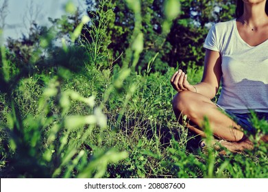 Yoga - Faceless young woman meditating in nature.
