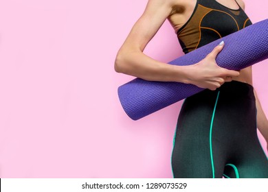 Yoga or fitness girl with yoga mat over pink background