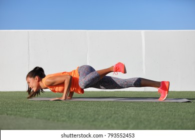Yoga fitness girl training triceps doing advanced push-up chaturanga with leg side crunch spiderman pose. Pushup exercise variation workout Asian woman on exercise mat outdoors. Happy active person.