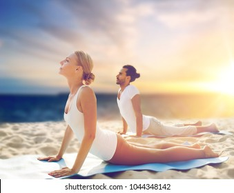 yoga, fitness and people concept - couple making cobra pose on beach