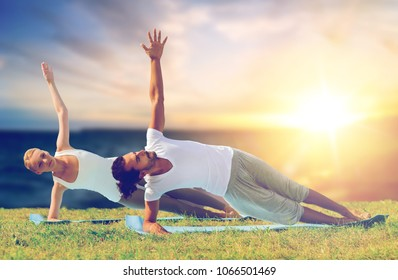 yoga, fitness and people concept - couple making side plank outdoors over sea background