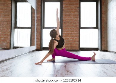 Yoga and fitness. Portrait of fit woman working out and practicing yoga at gym or studio with loft interior