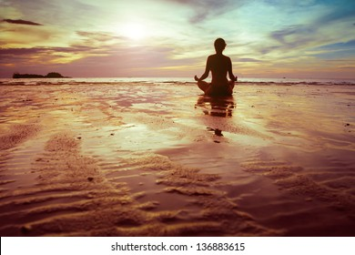 yoga and fitness, silhouette of woman meditating on the beach
