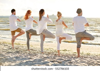 yoga, fitness, sport and healthy lifestyle concept - group of people in tree pose on beach