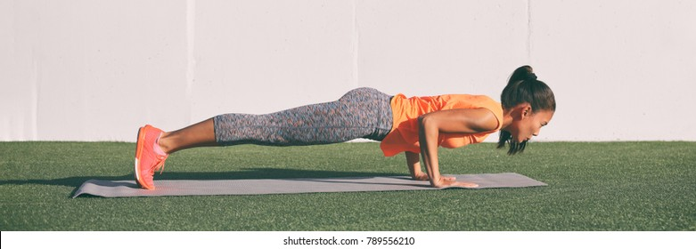 Yoga fitness woman practicing chaturanga pose push ups press up on exercise mat at outdoor home. Fit and healthy young girl doing morning core body workout pushup strength training. Banner panorama.
