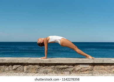 Yoga fitness woman stretching body, doing reverse plank pose - Purvottanasana outdoor with sea in the background in white swimsuit. Active, relaxing, calm vacation