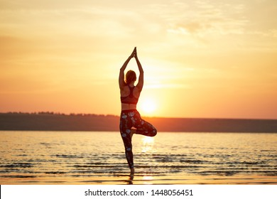 Yoga and fitness. Young woman practicing morning meditation in nature at the beach