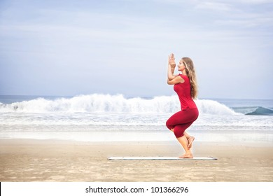 Yoga Garudasana eagle pose by young woman with long hair in red cloth on the beach at ocean background