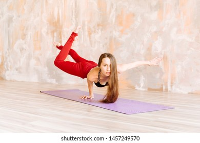 Yoga girl in black top and red leggings stands on one hand on the Mat