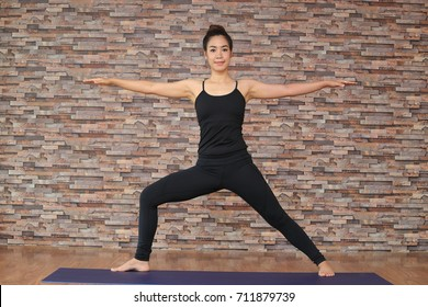 Yoga girl in class fitness wear black clothes in the brick wall