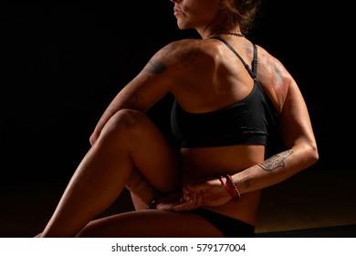 Yoga girl doing an asana on dark black background in ardha matsiendrasana