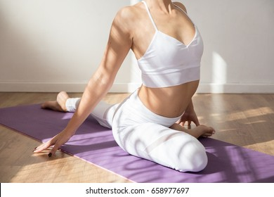 Yoga girl doing a stretching pose on a purple mat in a white studio space with beautiful warm morning light