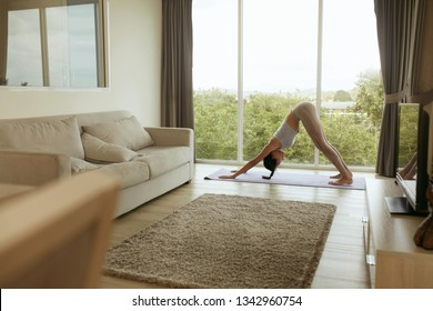 Yoga. Girl doing yoga training, stretching body at home in morning. Beautiful asian woman with fit body practices downward facing dog pose on yoga mat in living room indoors
