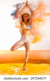 yoga girl makes poses in holi paints