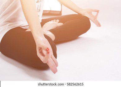 Yoga girl meditating indoor and making a zen symbol with her hand. Closeup of woman body in yoga pose. Toned