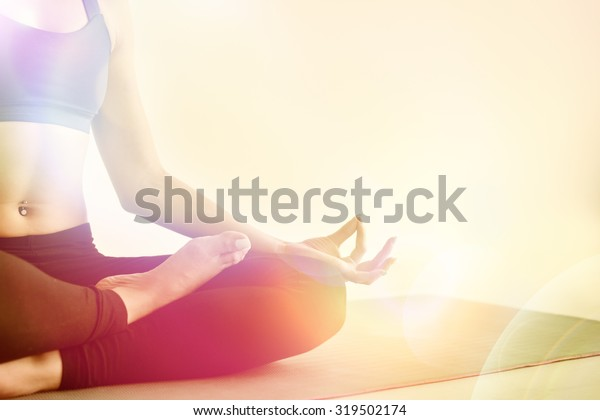 Yoga girl meditating indoor and making a zen symbol with her hand. Closeup of woman body in yoga pose Photo with color filters and warmth background.