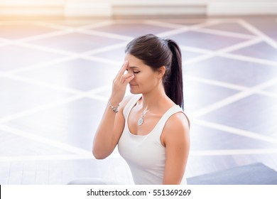 Yoga girl on fitness class background practicing nadi shodhana pranayama (Alternate, Nostril, Breathing) in lotus pose