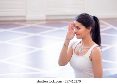 Yoga girl on fitness class background practicing nadi shodhana pranayama (Alternate, Nostril, Breathing) in lotus pose.