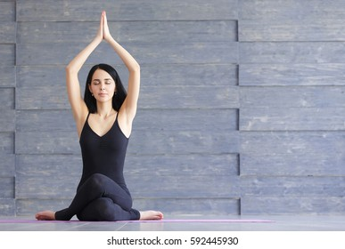 Yoga girl on fitness class background practicing nadi shodhana pranayama or Breathingin in gomukhasana asana or cow head pose