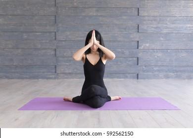Yoga girl on fitness class background practicing nadi shodhana pranayama or Breathingin in gomukhasana asana or cow head pose