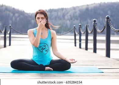 Yoga girl on nature background practicing nadi shodhana pranayama - Breathing in lotus pose. Relax and meditation on the lake