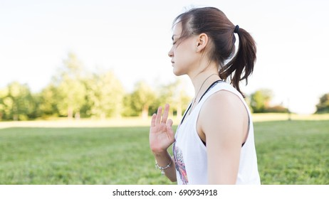 Yoga girl on nature background with green grass practicing nadi shodhana pranayama or Breathingin in gomukhasana asana or cow head pose at sunny day