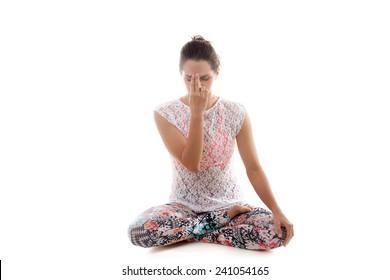 Yoga girl on white background practicing nadi shodhana pranayama (Alternate, Nostril, Breathing)