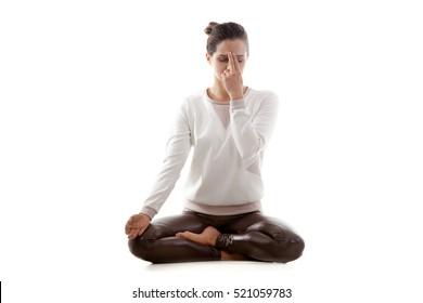 Yoga girl on white background practicing nadi shodhana pranayama (Alternate, Nostril, Breathing) sitting with crossed legs in lotus pose. Meditation, breathing exercises