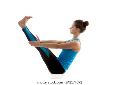 Yoga girl practices Boat Pose (Paripurna Navasana) in black and blue sportswear on white background