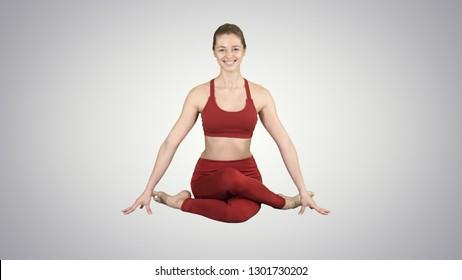 Yoga girl practicing nadi shodhana pranayama or Breathingin in gomukhasana asana or cow head pose on gradient background.