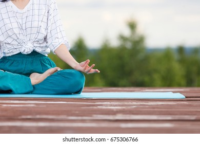 Yoga girl in the summer park meditation. Young woman relax and exercising in nature wooden pier with blue cloudy sky and green trees at background. Freedom, calm and yoga concept