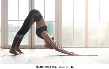 Yoga girl working out indoors, downward facing dog pose over big window in sun lights, panorama with copy space