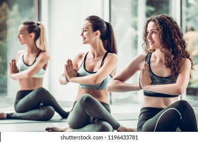 Yoga girls on fitness class background practicing nadi shodhana pranayama or Breathingin in gomukhasana asana or cow head pose