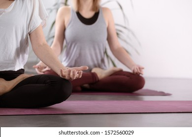 Yoga group concept. People meditating together, sitting back to back on windows background, copy space