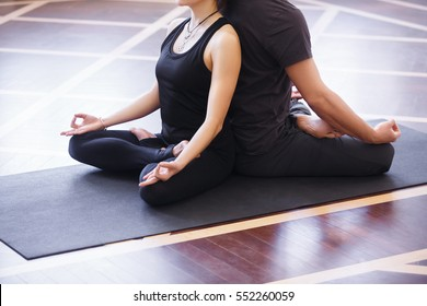 Yoga group concept. Young couple meditating together, sitting back to back on windows background