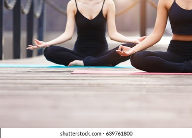 Yoga group concept. Young couple meditating together, sitting back to back on nature background, copy space