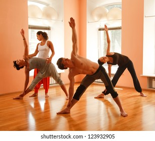 Yoga group practicing under instructors guidance