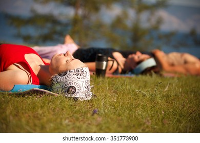 Yoga group relaxing on the grass.Young woman on the foreground.Selective focus