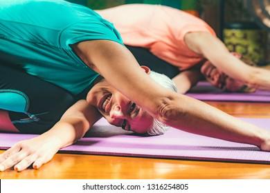 Yoga guru with senior woman, doing yoga