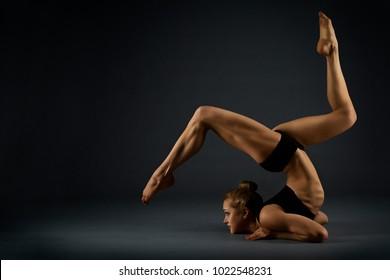 Yoga Gymnastics Pose, Woman Flexible Body, Gymnast Balance in Backbend Exercise, Acrobat Back Bend Position, Girl Posing on Black Background