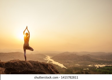 Yoga in Hampi temple copyspase at sunset.travel vacation copy spase lady with stylish jumpsuit