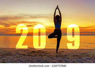 Yoga Happy new year card 2018. Silhouette woman practicing yoga standing as part of Number 2019 on the beach at sunset. Healthy & Holiday Concept.