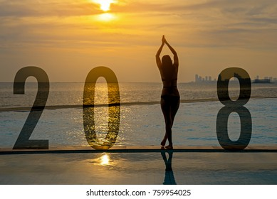 Yoga Happy new year card 2018. Silhouette woman practicing yoga on swimming pool standing as part of Number 2018 near the beach at sunset.  Healthy & Holiday Concept.