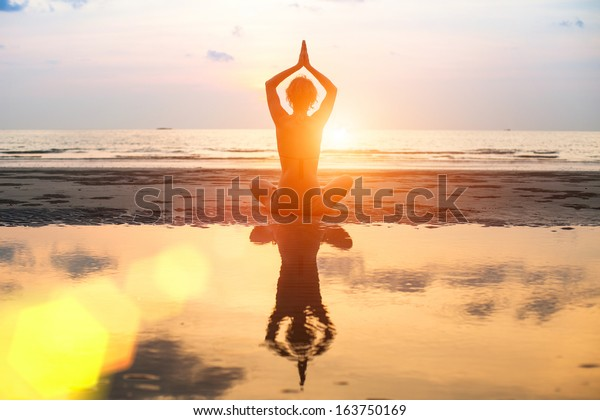 Yoga, harmony of health, silhouette young woman on the beach at sunset.