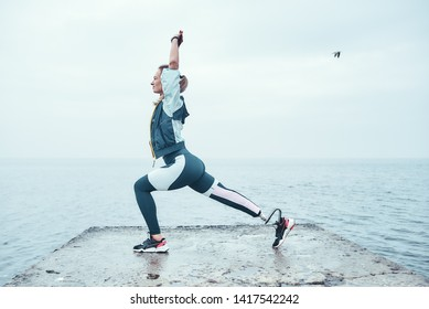 Yoga for health. Sporty disabled athlete woman in sportswear with prosthetic leg standing in yoga pose on the stone in front of the sea.
