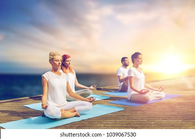 yoga and healthy lifestyle concept - group of people meditating in lotus pose on wooden pier over sea background